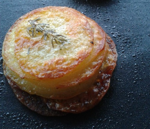 In de oven gebakken aardappelplakjes met roomboter, knoflook en tijm.