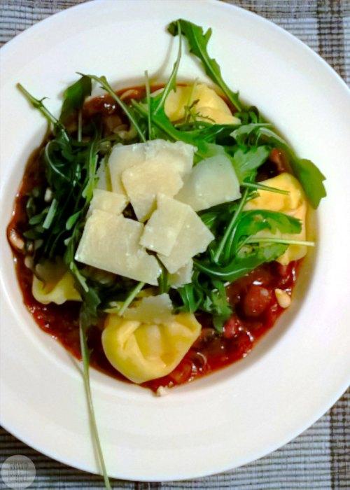 Een snel winters gerecht: gevulde pasta met champignons in tomatensaus, rucola en Parmezaanse kaas.