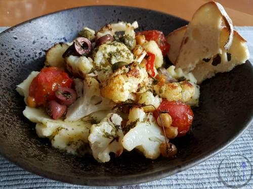 Een traybake van bloemkool met kikkererwten en tomaatjes, erover een dressing met kappertjes en olijven. Geserveerd met aardappelpuree voor een heerlijke vleesloze maaltijd.