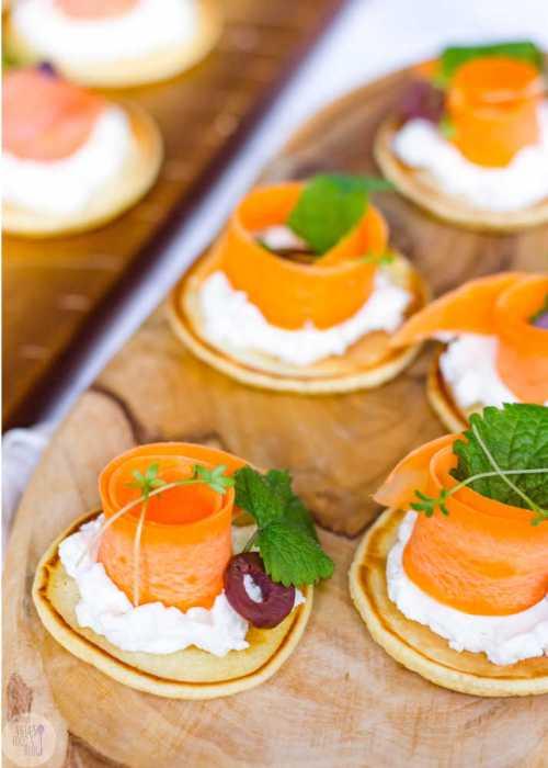 Deze hartige blini's met gerookte zalm en mierikswortel, wortel met geitenkaas of pastinaak met humus zien er niet alleen prachtig uit, ze smaken ook super! #recept #blini's #gerooktezalm #groenten #feestelijk