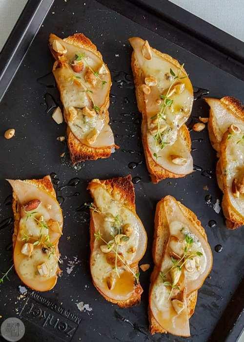 Deze crostini met peer en gorgonzola is een gouden combinatie. De crostini maak je trouwens heel gemakkelijk ook van Turks brood. Rooster zeker ook een handje noten en druppel er een sliert ahornsiroop over. Succes verzekerd!