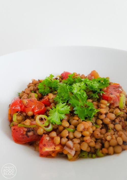 Deze linzen met tomaat en lente-ui krijgen extra smaak door kruiderij en zwarte knoflook. Een heerlijk bijgerecht dat ook prima als vleesvervanger op tafel gezet kan worden.   #recept #linzen #vegetarisch #vegan #makkelijk #gezond