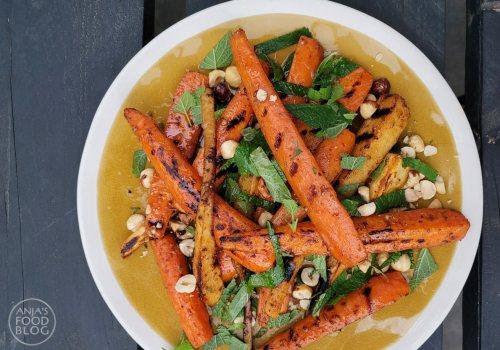 Steek de BBQ maar aan: gegrilde worteltjes en pastinaak met specerijen en een dressing van ahornsiroop, citroenmelisse en hazelnoten. Het recept is afkomstig uit De Groene Barbecue van Rukmini Iyer.